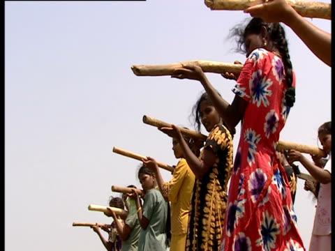 A group of women train using sticks as guns