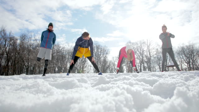 Group of young athletes warming up on a snow  before sports training.