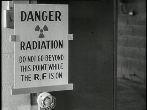 A group of young children hide under a desk as a siren and flashing light send an alert about radiation