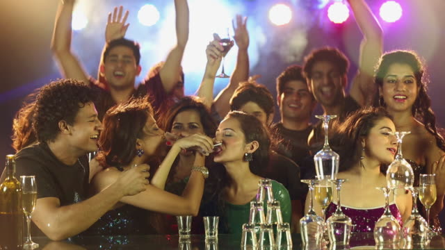 Group of young friends drinking tequila at nightclub party