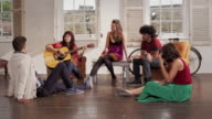 WS group of young men and women sitting in loft , young woman playing guitar handheld