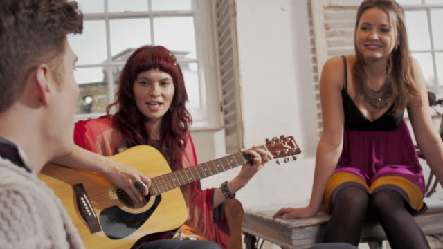 MS group of young men and women sitting in loft , young woman playing guitar handheld