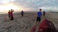 A group of young men playing flag football on the beach. - Slow Motion
