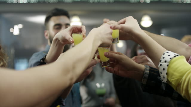 Group of young people dance and drink cocktails