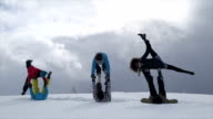 Group of young people performing acrobatic yoga in a mountain setting