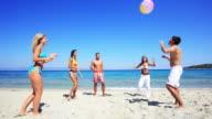 Gruppe von jungen Menschen spielen ball am Strand.