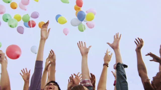 Group of young people releasing balloons
