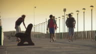 WS Group of young people running and skateboarding on beach promenade at sunset / Cape Town, Western Cape, South Africa