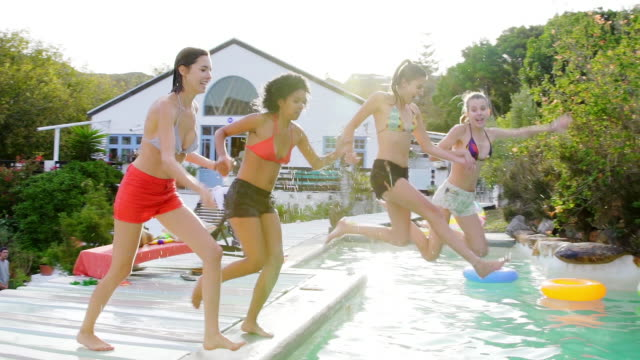 Group of young women  jumping into swimming pool