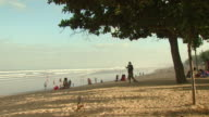 WS Group off people on beach, two men sweeping / Bali, Indonesia