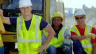 MS, PAN, group portrait of construction workers standing and sitting by earth mover, San Antonio, Texas, USA