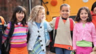 MS PAN Group portrait of school students (4-7) standing in a row in front of school bus / Richmond, Virginia, USA