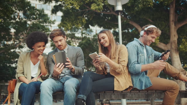 Group sitting on bench with their mobile devices