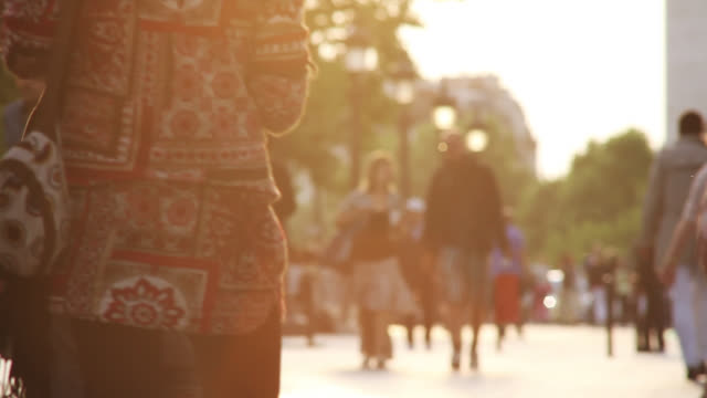 Groups of pedestrians converse as they stroll down the Avenue des Champs-Elysees.