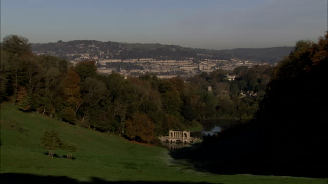 A grove of trees separates a lush valley and the city of Bath. Available in HD.