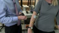 UK growth forecast downgraded by IMF Oxfordshire Wantage EMS Physio INT James Greenham applying electodes to reporter's arm as demonstrating item of...