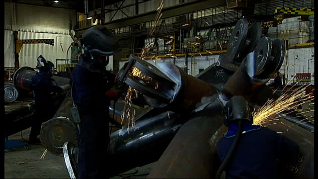 GDP growth of 05% raises concern about recession Feb 2011 / R25021116 Bolton INT Various workers on factory floor welding and grinding sections of...