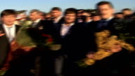 Severny Airport EXT Plane taxiing on runway with crowd of onlookers in the foreground Kadyrov next officials holding bouquets of flowers Armed...