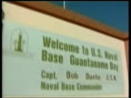 Guantanamo Bay detainee treatment ITN Guantanamo Bay Flag flying over entrance to Guantanamo Bay US naval base TILT DOWN welcome sign FADE TO