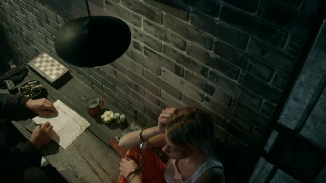 Guard interrogating women in jail