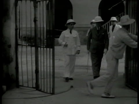 Guard opening gate unidentified Frenchman in suit walking w/ officials in white uniforms through prison talking w/ prisoner French penal colony harsh...