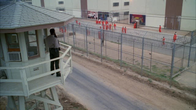 WS Guard with rifle standing in guard tower and people of wearing orange uniforms in prison yard