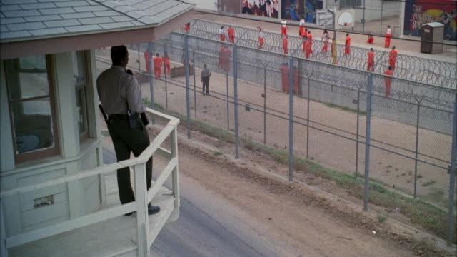 MS Guard with rifle standing in guard tower and people of wearing orange uniforms in prison yard
