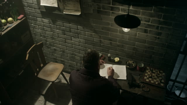 Guard writing down information about convicts in prison
