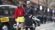 A guest a red pull over and a yellow skirt outside House of Holland during London Fashion Week September 2017 on September 16 2017 in London England