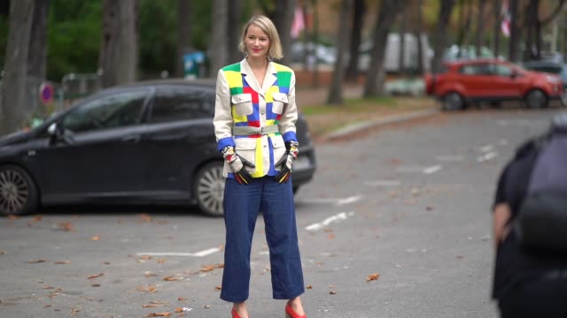 A guest wears a beige safari jacket with yellow green red and blue empiecements big hoop earrings outside Lanvin during Paris Fashion Week Womenswear...