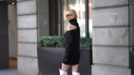 A guest wears a black off shoulder top silver sunglasses white leather thigh high boots with the printed inscription 'For Walking' outside Peter...