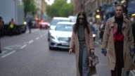A guest wears a camel coat and gray pants outside House of Holland during London Fashion Week September 2017 on September 16 2017 in London England