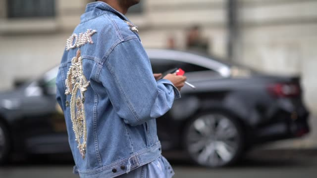 A guest wears a denim jacket with embroidery 'KOJAK' outside Manish Arora during Paris Fashion Week Womenswear Spring/Summer 2018 on September 28...