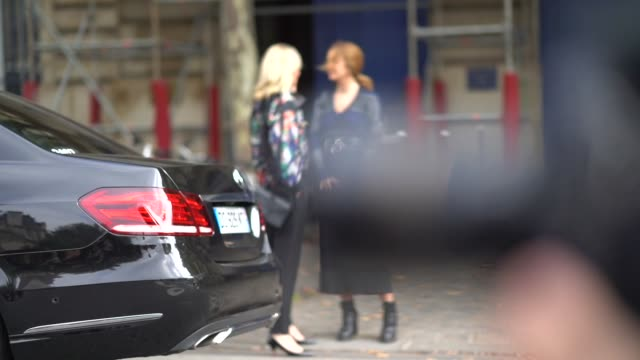 A guest wears a flower print top black pants a black bag black shoes a guest wears a grey and blue Vneck long dress a black belt a studded black bag...