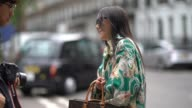 A guest wears a green jacket with printed flowers a Vuitton bag with the inscription 'Emily' a white ruffled skirt during London Fashion Week...