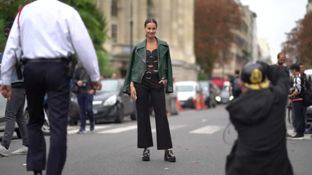 A guest wears a green leather jacket a beige and black openwork top black flare pants black studded platform clogs outside Lanvin during Paris...