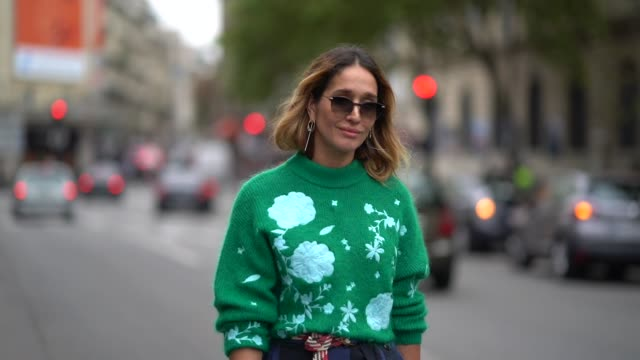 A guest wears a green pull over a blue skirt red shoes outside the Dries Van Noten show during Paris Fashion Week Womenswear Spring/Summer 2018 on...