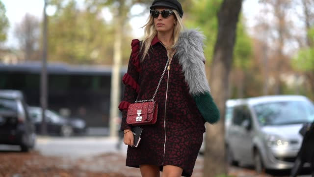 A guest wears a grey hat a white and dark green fur scarf a red and black print coat with red flounces a red studded Dior bag black suede over the...