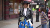 A guest wears a hat a black perfecto leather jacket a blue skirt outside JW Anderson during London Fashion Week September 2017 on September 16 2017...