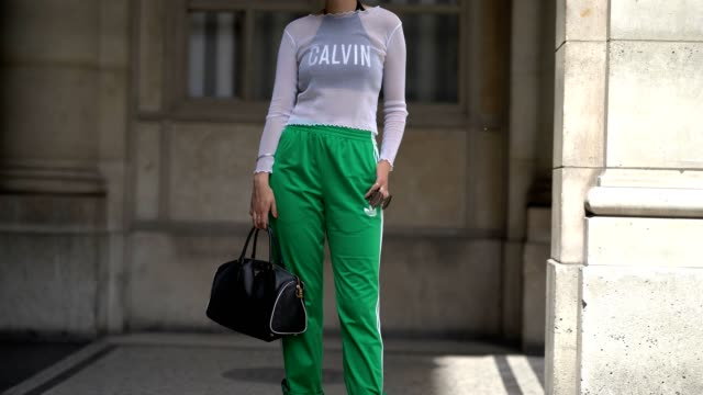 A guest wears a mesh top Calvin black bra Adidas green sportswear pants a Prada bag and black boots outside the Louis Vuitton show during Paris...