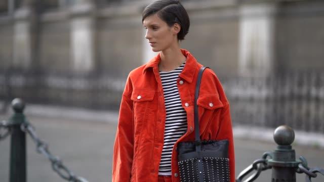 A guest wears a striped top an orange corduroy pantsuit a black bag black sneakers outside the Dries Van Noten show during Paris Fashion Week...