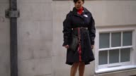A guest wears a The North Face coat a Gucci belt a Balenciaga clutch and black platform shoes outside Simone Rocha during London Fashion Week...