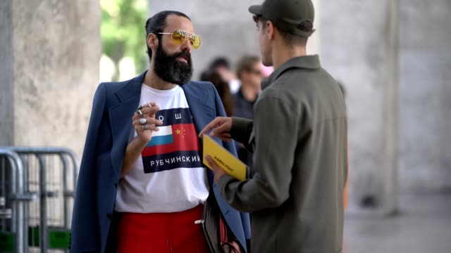 A guest wears a Tommy Hilfiger tshirt a blue blazer jacket red sportswear pants clear yellow sunglasses outside the 22/4 Hommes show during Paris...