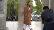 A guest wears a trench coat outside the Lemaire show during Paris Fashion Week Womenswear Spring/Summer 2018 on September 27 2017 in Paris France