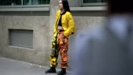A guest wears a yellow bomber jacket military camouflage print pants black boots a bare belly black top outside the Y3 show during Paris Fashion Week...