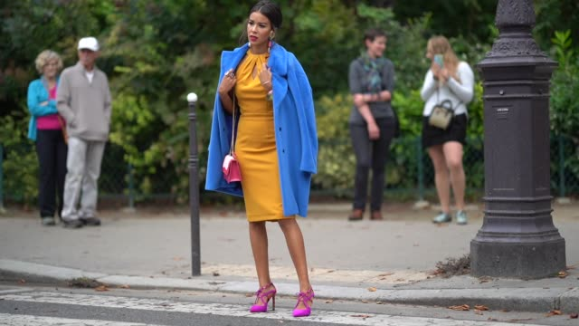 A guest wears big earrings a royal blue coat an ochre yellow raglan dress a pink bag pink shoes outside Lanvin during Paris Fashion Week Womenswear...