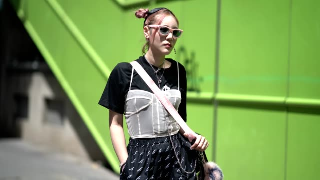 A guest wears pink sunglasses flared pants a black tshirt outside the Y3 show during Paris Fashion Week Menswear Spring/Summer 2018 on June 25 2017...