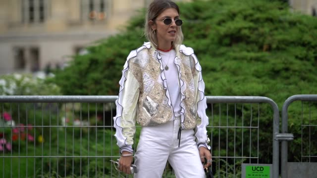 A guest wears sunglasses a beige and white flounced jacket a black bag white baggy ripped pants red patent leather shoes outside Lanvin during Paris...