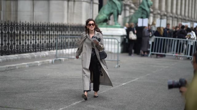 A guest wears sunglasses a black and white houndstooth trenchcoat a grey Vneck top a black bag black shiny baggy pants black shoes outside the Dries...