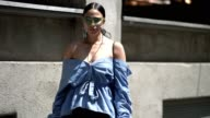A guest wears sunglasses a blue striped offshoulder top sportswear pants and black shoes outside the Y3 show during Paris Fashion Week Menswear...
